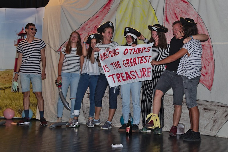 "A youth group during their pirate-themed stage play, holding a sign saying ""helping others is the greatest treasure""."