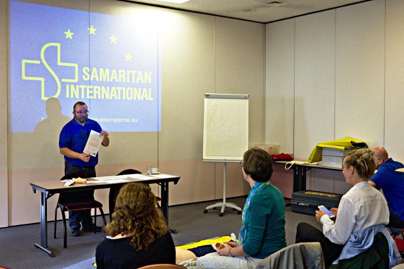 Szene aus einem der Erste-Hilfe-Kurse - Ein Ausbilder steht vor einem Präsentationsschirm, mehrere Teilnehmerinnen folgen der Erklärung.
