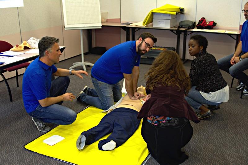 Szene aus einem der Erste-Hilfe-Kurse - Zwei Ausbilder und zwei Teilnehmerinnen hocken um eine CPR-Übungspuppe. Die Ausbilder erklären und demonstrieren die Herz-Lungen-Wiederbelebung.